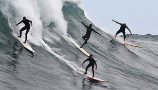 Four men in wetsuits with surfboards